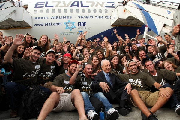 Israel's President Shimon Peres, who celebrated his 87th birthday this week, gets down on the tarmac at Ben Gurion Airport to help greet 85 new recruits to the IDF who arrived on the August 3rd Nefesh B'Nefesh charter flight.
