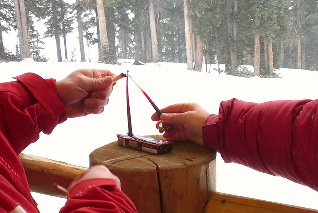 Jeff Finkelstein puts matches to the first night's candles, held by Rabbi Jamie Korngold, at Copper Mountain.