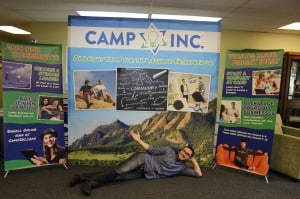 Boulder JCC Executive Director poses in front of the Camp Inc. conference set-up.