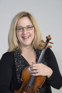 Headshot of Cookie Segelstein with a violin/viola